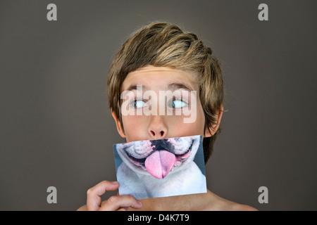 Junge mit Bild des Hundes über Gesicht - Stockfoto