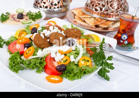Falafel-Salat mit Fladenbrot und Hummus Platte, ergänzt mit Tee auf einer weißen Tischdecke. - Stockfoto
