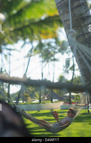 Mann in der Hängematte unter Palmen - Stockfoto