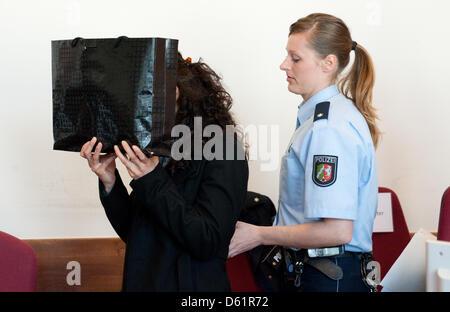 Ein Angeklagter verbirgt sich hinter einer Tasche vor der Verhandlung am Landgericht in Detmold, Deutschland, 30. - Stockfoto