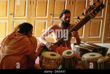 """Ein hinduistischer Mönch (""""Sadhu"""") spielt Sitar, während ein Neuling hört. Beide gehören der Swaminarayan-Sekte - Stockfoto"""