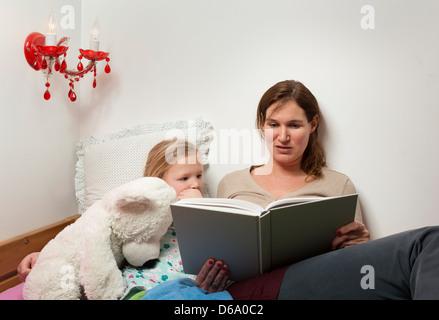 Mutter Tochter im Bett lesen - Stockfoto