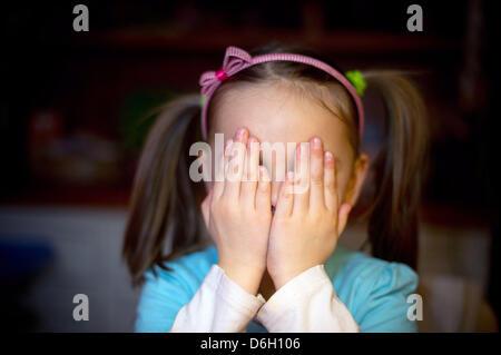 Eine fünf-jähriges Mädchen sitzt am Tisch der elterlichen Hause und verbirgt ihr Gesicht in Sieversdorf, Deutschland, - Stockfoto