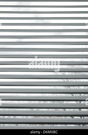 Bäume durch halb geschlossenen metallischen Jalousien in einem Fenster gesehen. - Stockfoto