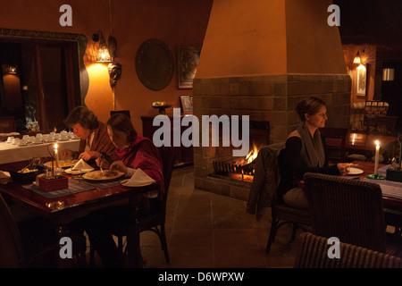 Holz Im Kamin · Menschen, Die Neben Großen Kamin In Warm Beleuchteten Raum  Essen   Stockfoto