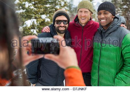 Menschen nehmen Foto von Freunden draußen im winter - Stockfoto