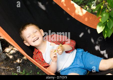 Kleinen Jungen auf dem Rücken in einer Hängematte unter einem schattigen Baum genießen das sonnige Frühlingswetter - Stockfoto