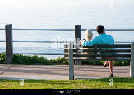Junges Paar auf einer Bank sitzend - Stockfoto