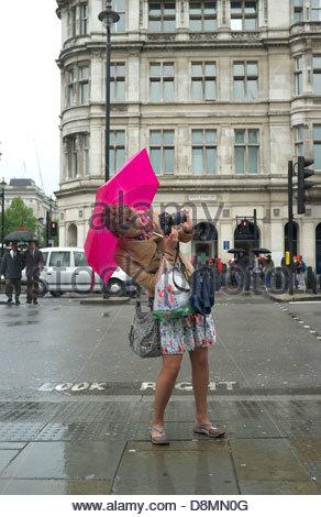Ein Tourist mit dem Fotografieren im strömenden Regen, in Westminster, London, UK. - Stockfoto