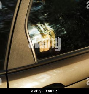 Ein skandinavisches Mädchen mit einer Krone im Haar Blick aus einem Autofenster, Schweden. - Stockfoto