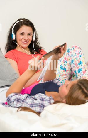 Beste Freunde, faulenzen und lesen auf Bett - Stockfoto