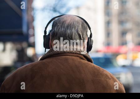 Rückansicht des älteren Menschen tragen von Kopfhörern - Stockfoto