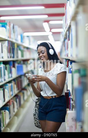 Studentin, anhören von MP3-Player in Bibliothek - Stockfoto
