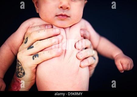 Vater mit tätowierten Händen halten Baby boy - Stockfoto