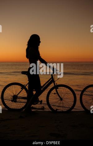 Silhouette der Frau auf seinem Fahrrad am Strand - Stockfoto