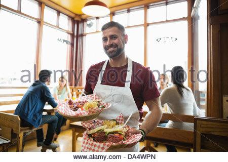 Porträt von männlichen Deli Inhaber hält Essen im restaurant - Stockfoto