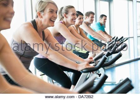 Menschen, die Ausübung auf stationären Fahrrädern in Fitness-Klasse - Stockfoto