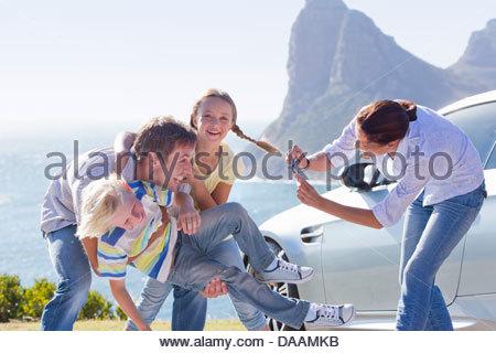 Mutter fotografieren glückliche Familie spielen im freien Auto in der Nähe von Meer - Stockfoto