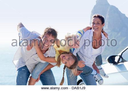 Porträt der glückliche Familie neben Auto mit Meer im Hintergrund - Stockfoto