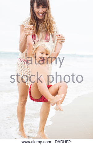 Mutter schwingenden Kind am Strand - Stockfoto