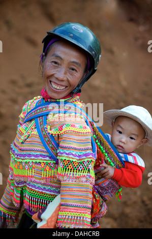 Flower Hmong Frau mit Kind in markanten tribal Kostüm. Können Sie Cau, in der Nähe von Bac Ha.  Vietnam. Modell - Stockfoto