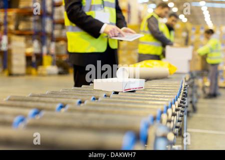 Arbeitnehmer, die Pakete auf Förderband im Lager überprüfen - Stockfoto