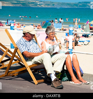 Paar, sitzen in Liegestühlen am Strand von Weymouth, Dorset, UK lesen. - Stockfoto