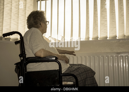 Neunzig Jahre alte Dame mit Hand am Kühler Blick aus Fenster in ihrem eigenen Zuhause. England, UK - Stockfoto