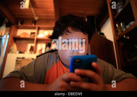 Ein neun Jahre alter Junge mit einem Apple IPod iPodTouch oder IPhone iPhone oder IPad tragbaren Media-player - Stockfoto