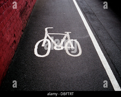Zyklus-Weg-Symbol auf einem britischen Gehweg Pflaster. Eine durchgezogene Linie trennt den Radweg von der Fussweg. - Stockfoto