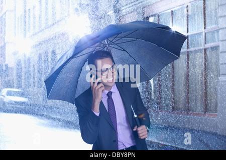 Glücklich Kaufmann reden über Handy unter Dach im verregneten Straße - Stockfoto