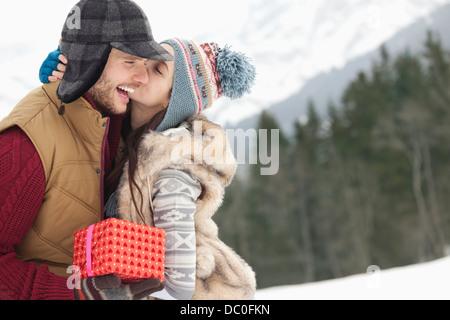 Brautpaar mit Weihnachten Geschenk kissing in schneebedecktes Feld - Stockfoto
