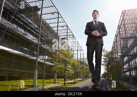 Übergroße Geschäftsmann zu Fuß unterwegs, niedrigen Winkel Ansicht - Stockfoto