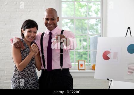 Bürokollegen zeigen und lächelnd in treffen - Stockfoto