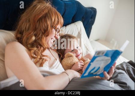 Mutter und Tochter Lesebuch im Bett liegend - Stockfoto