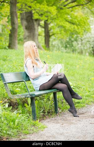 Eine junge attraktive Frau sitzen auf Bank in einem Park in ein Tagebuch zu schreiben - Stockfoto
