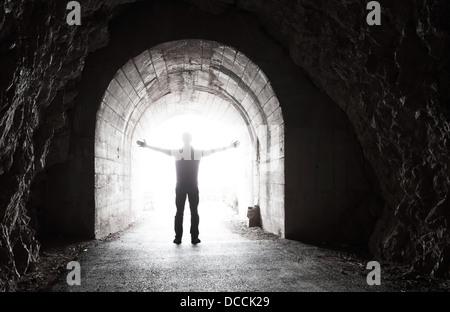 Der Mensch steht im dunklen Tunnel mit glühenden Ende - Stockfoto