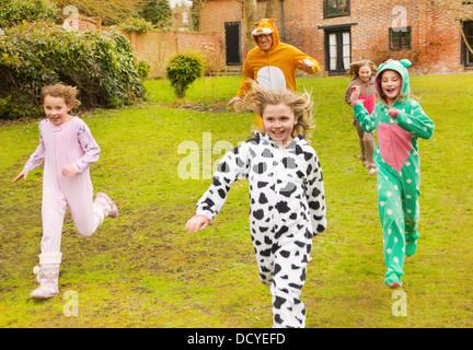 Mann und Mädchen tragen Tierkostüme im Garten laufen - Stockfoto