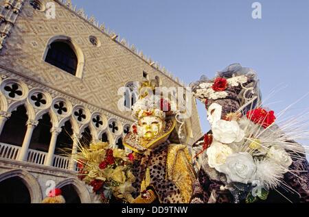 Zwei Personen bei San Marco gekleidet in üppigen bunten Kostümen für eine Maskerade an Karneval. Venedig, Italien - Stockfoto