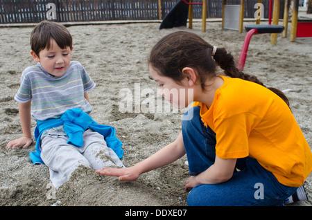 Zwei Kinder spielen im Sand am Strand in Spanien - Stockfoto