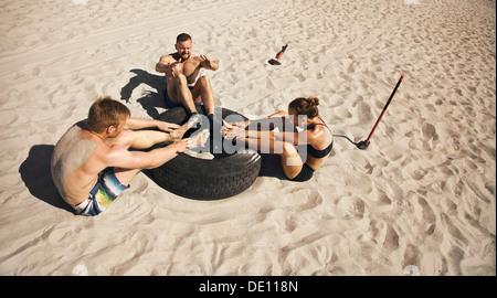 Fitness und gesunde Lebensweise. Kleine Gruppe von jungen Athleten, die Bauch-Übung mit einem LKW-Reifen am Strand - Stockfoto