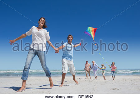 Glückliche Familie mit Drachen laufen am Sonnenstrand - Stockfoto