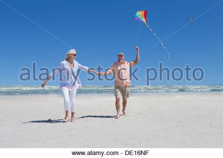 Gerne älteres paar Hand in Hand und fliegen kite am Sonnenstrand - Stockfoto