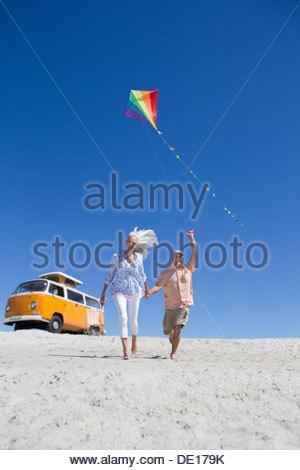 Gerne älteres Paar mit Drachen am sonnigen Strand mit van im Hintergrund laufen - Stockfoto