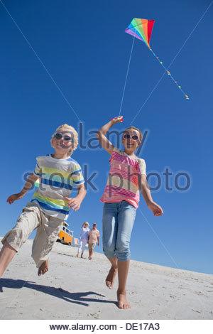 Jungen und Mädchen mit Drachen laufen am Sonnenstrand - Stockfoto