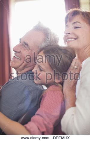Glückliche Großeltern und Enkelin umarmt - Stockfoto