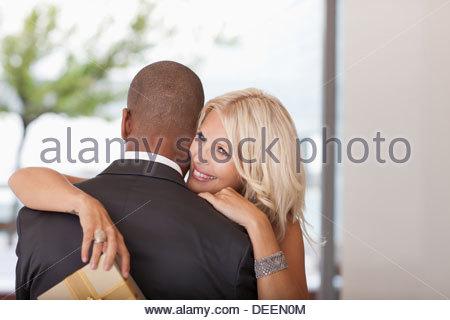 Frau mit Geschenk Mann umarmt - Stockfoto