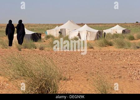 Zwei Frauen aus Nomadenfamilie, tragen die Mulafa, die mauretanischen Tracht zu Fuß zurück zu ihrem Zelt Haus in - Stockfoto