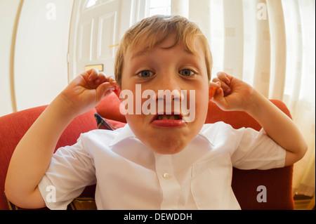 Ein 10 Jahre alter Junge ziehen ein lustiges Gesicht im Innenbereich - Stockfoto