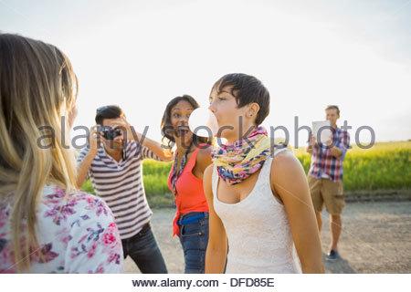 Fröhliche Freunde Blick auf Frau bläst Kaugummi - Stockfoto